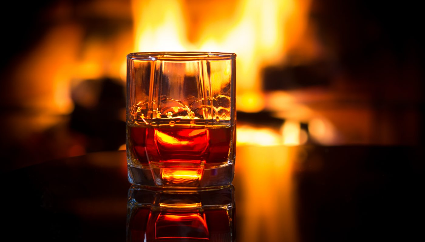 Glass alcoholic drink wine in front warm fireplace.